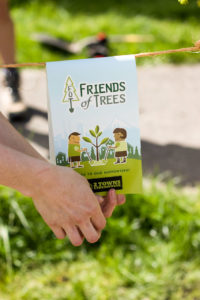 """A close up of a """"Friends Of Trees - Sponsored by 2 Towns Ciderhouse"""" sticker around a freshly planted tree."""